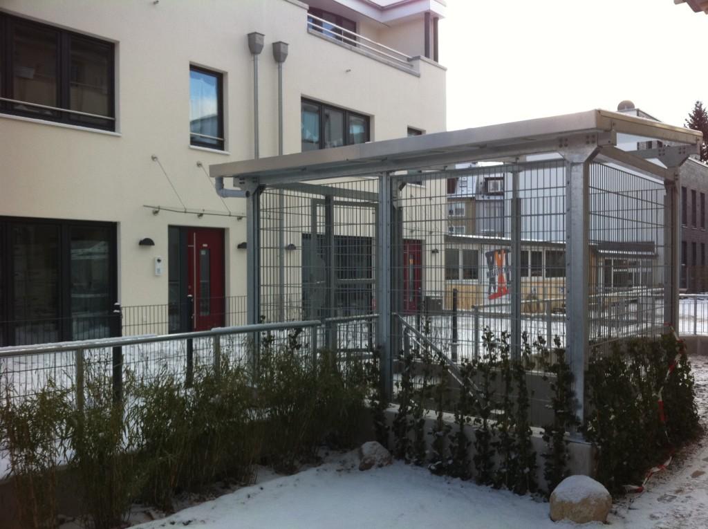 Pavillon aus verzinktem Stahl mit Glasüberdachung für den Tiefgaragenzugang