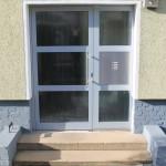 Hauseingangstür aus pulverbeschichtetem Aluminiumprofil mit großen Glasfüllungen
